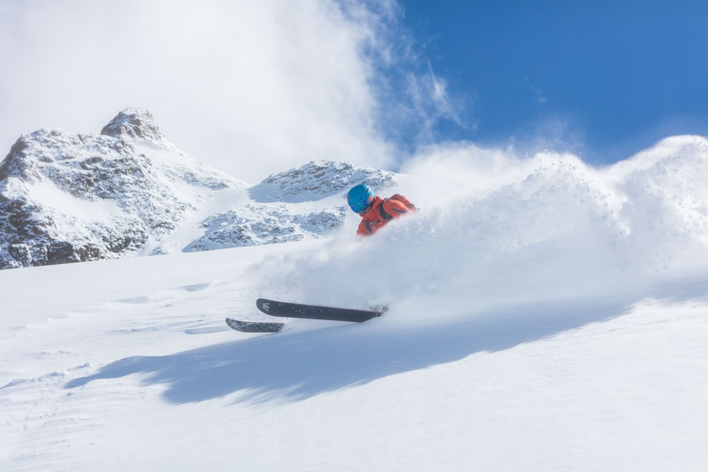 person in red jacket and black pants riding on black snowboard on snow covered mountain during