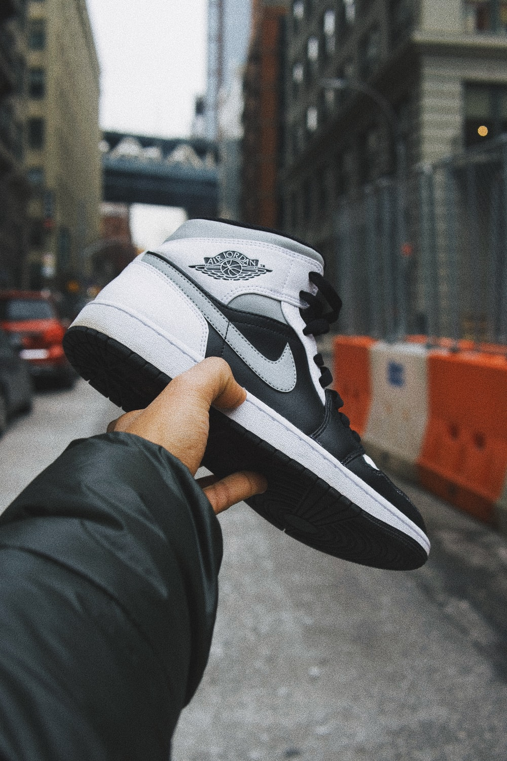 person holding white and black nike basketball shoes
