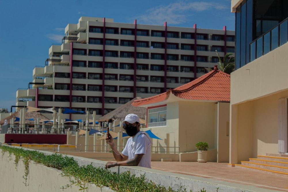 man in white t-shirt sitting on white concrete bench during daytime