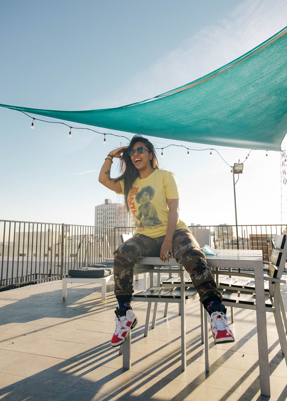woman in yellow t-shirt and black pants sitting on white wooden bench during daytime
