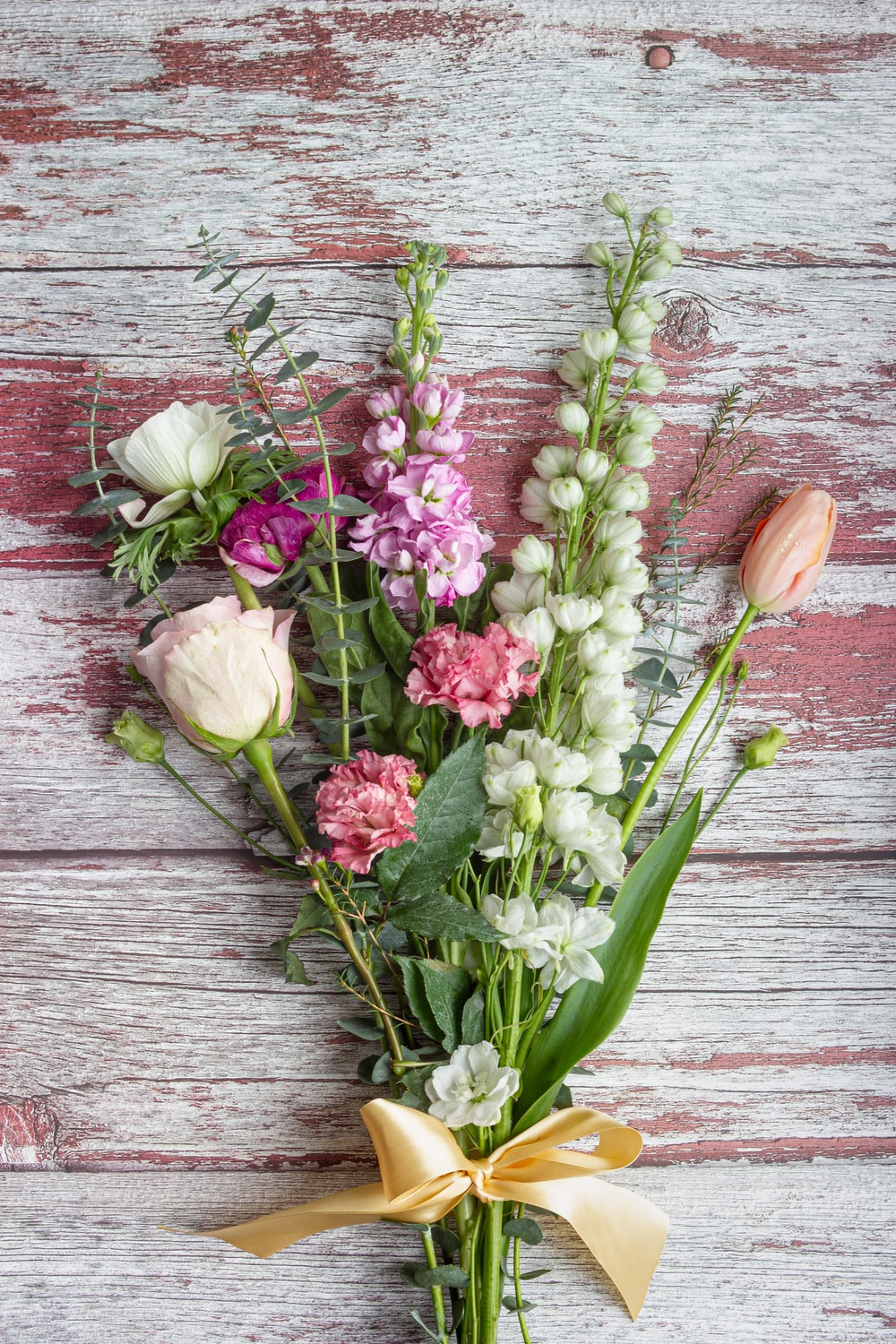 pink and white tulips on brown wooden surface