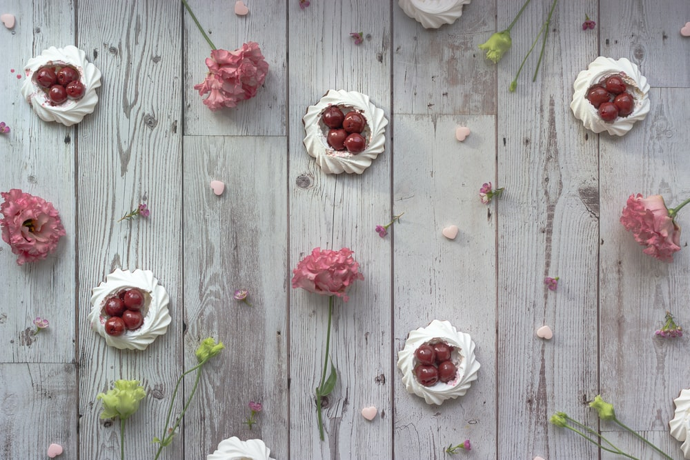 white and red roses on gray wooden surface