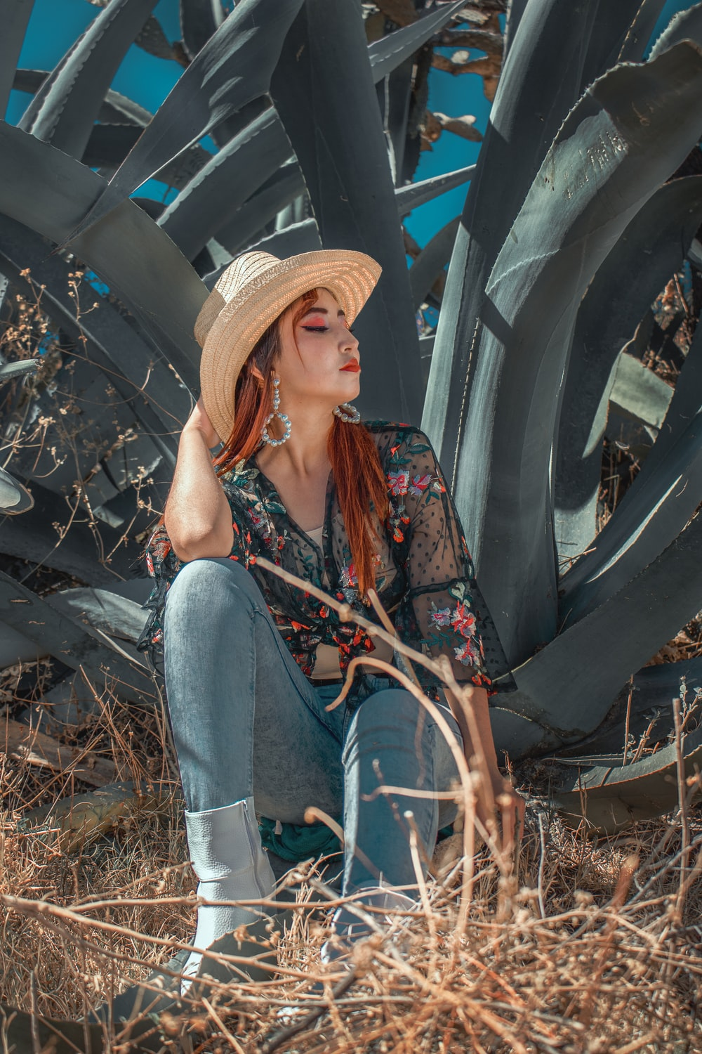 woman in blue denim jeans and brown hat sitting on brown dried leaves