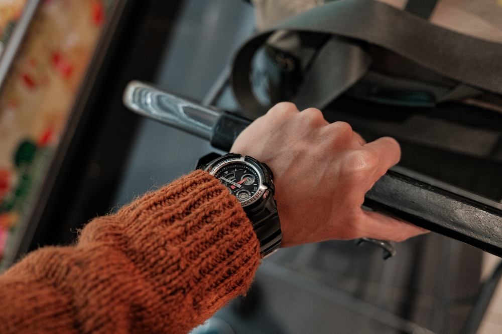 person in red sweater holding black steering wheel