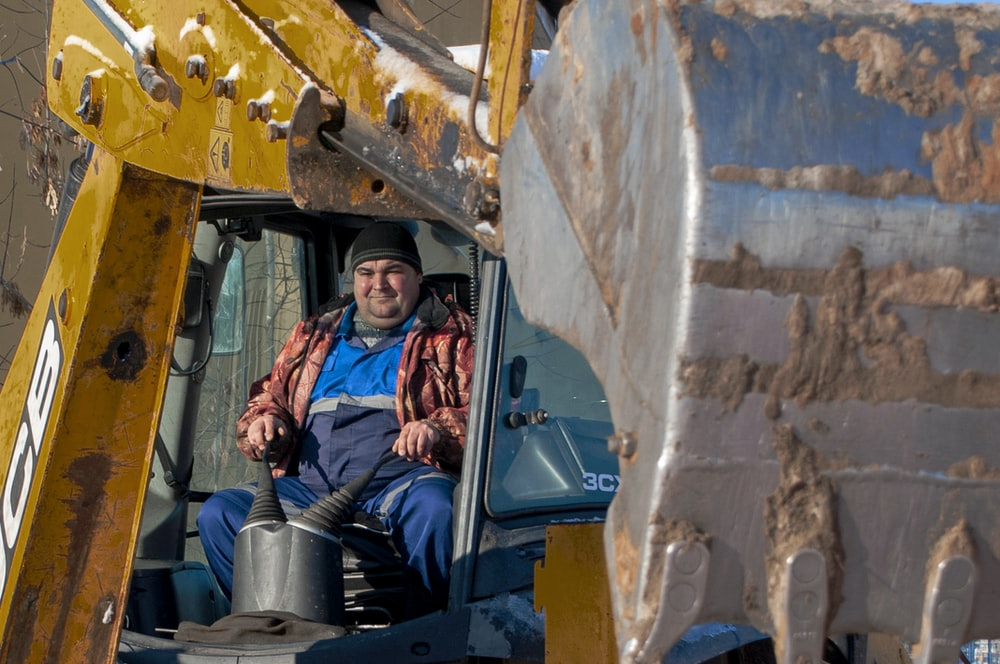 woman in black jacket and blue denim jeans riding on blue and black heavy equipment
