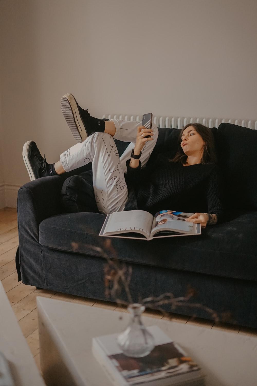 man and woman lying on black sofa