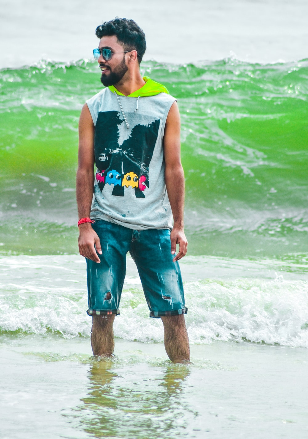 man in green tank top and blue shorts standing on seashore during daytime