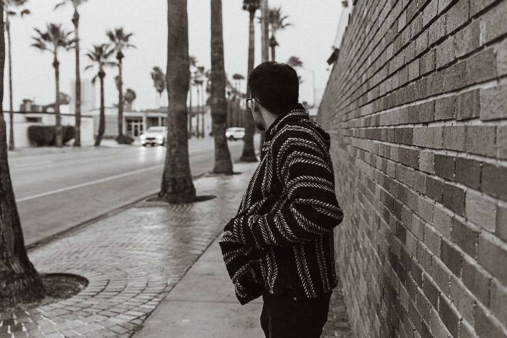 man in black and white striped hoodie standing beside concrete wall during daytime