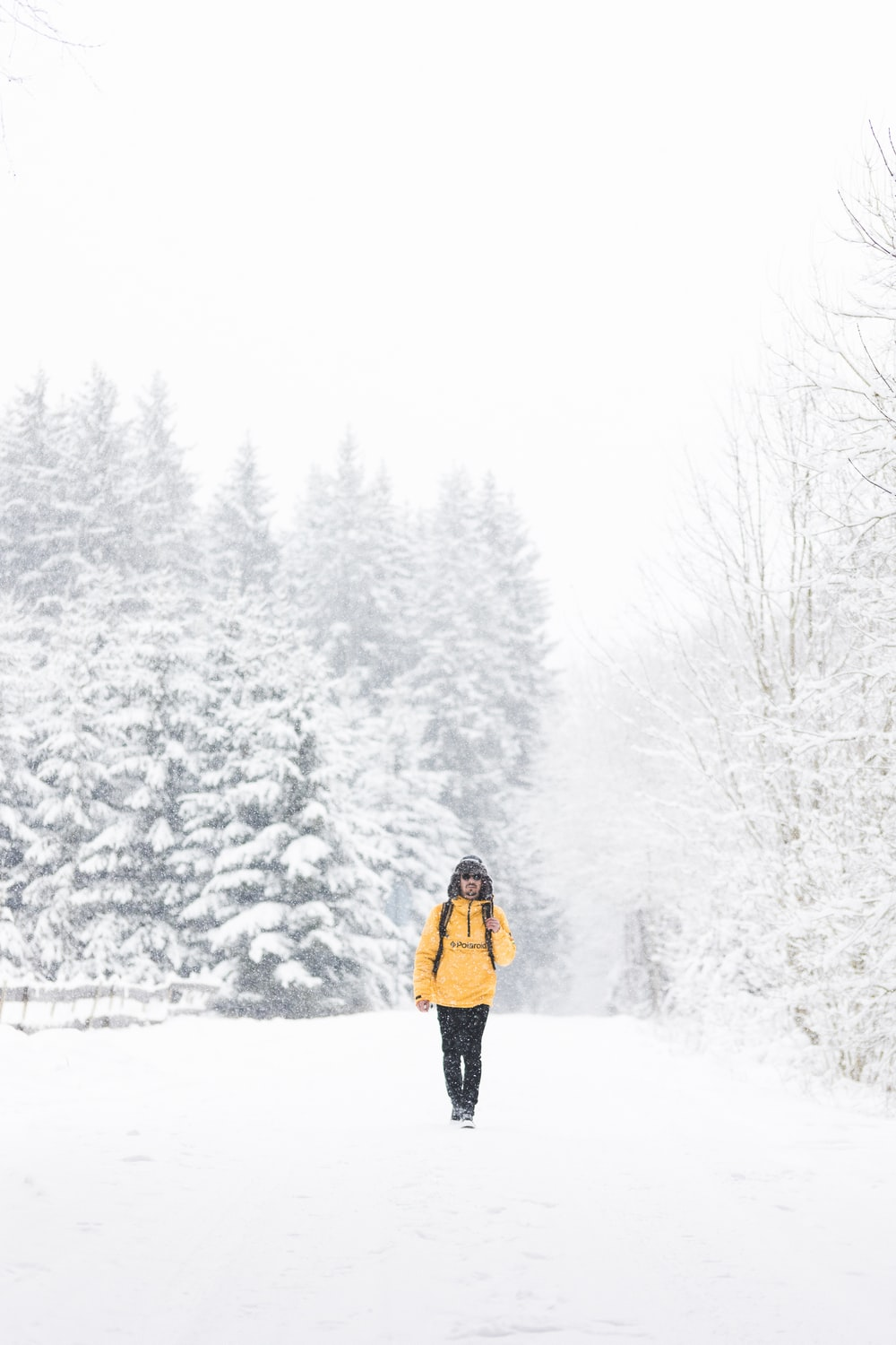 woman in yellow jacket and black pants standing on snow covered ground during daytime