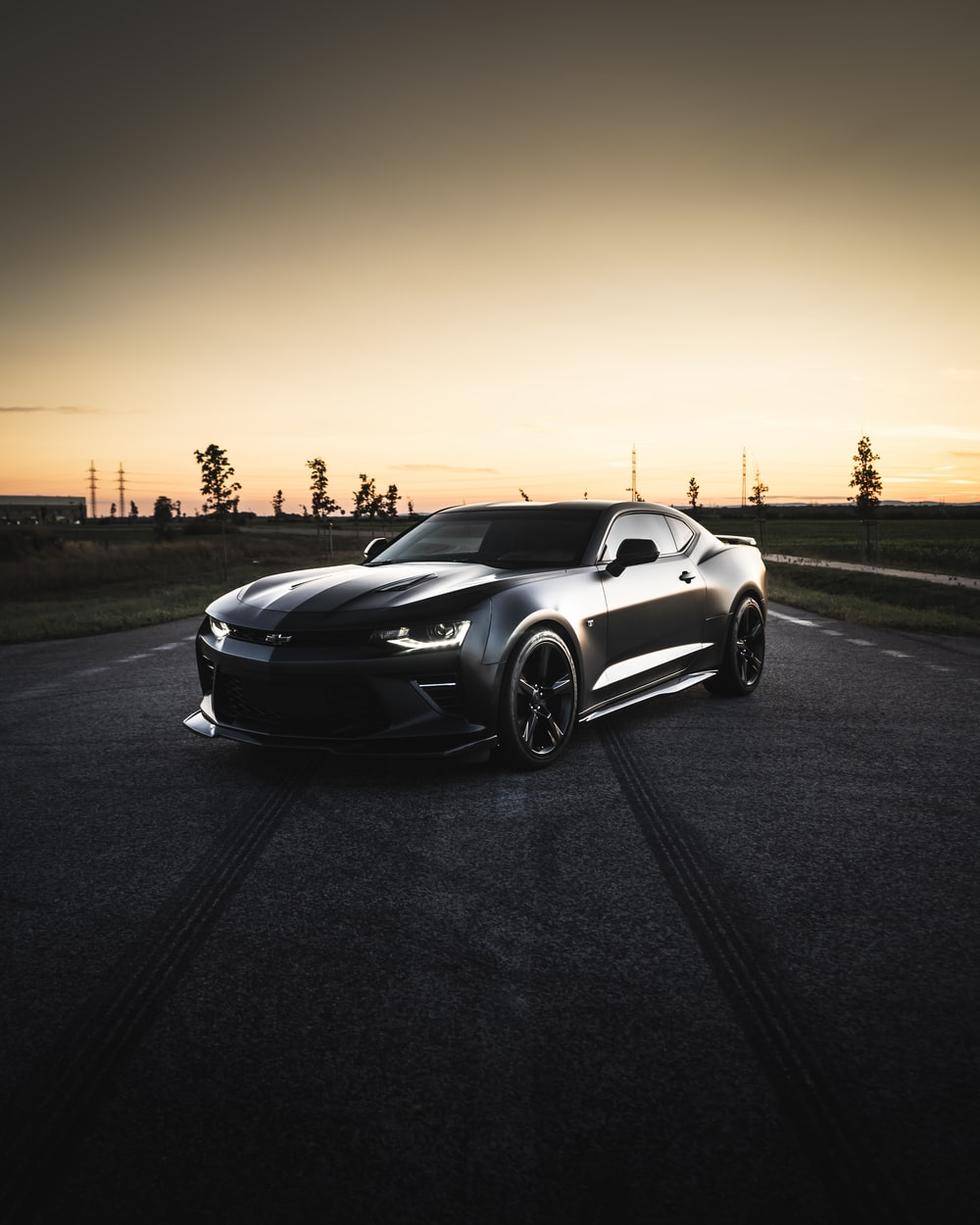 black coupe on road during sunset