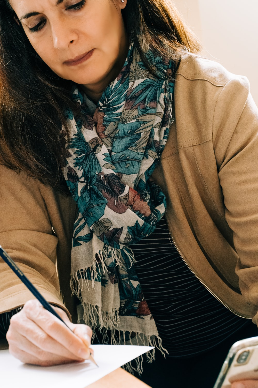 woman in brown coat with black white and red scarf