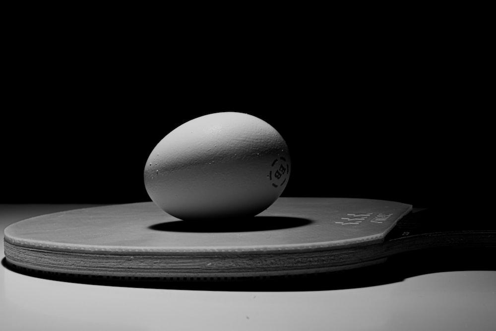 white ball on black round plate