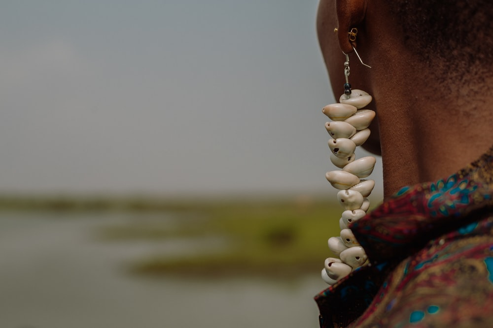 person holding white beaded necklace