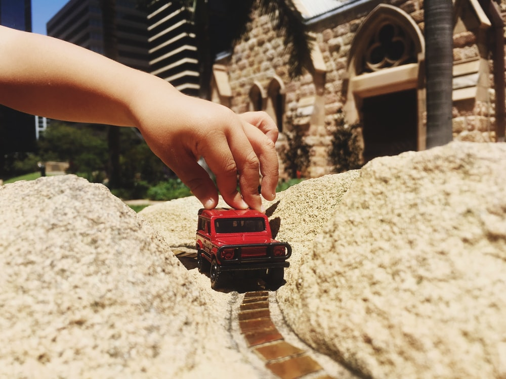 person holding red and black toy car