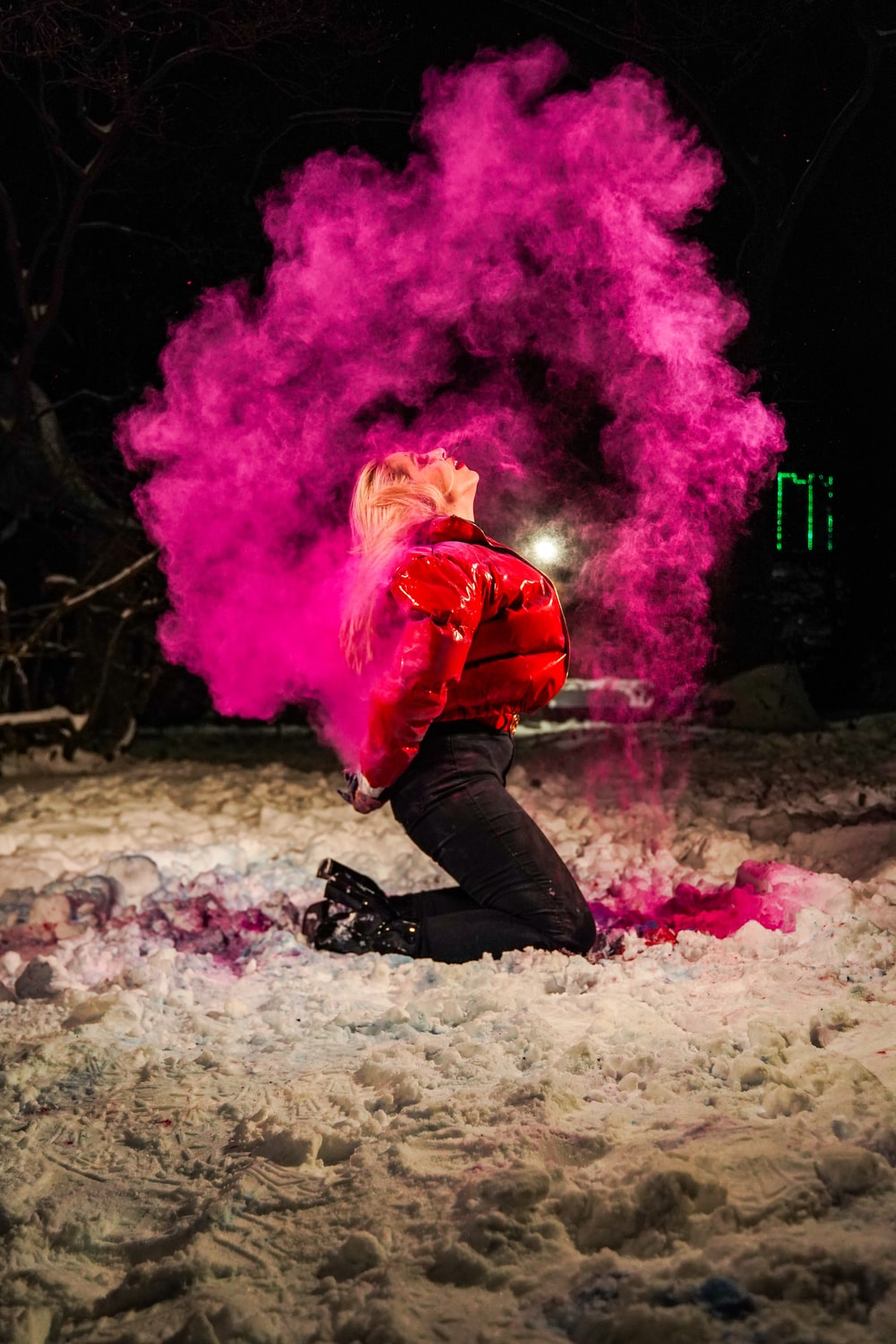 man in red jacket and black pants with pink smoke