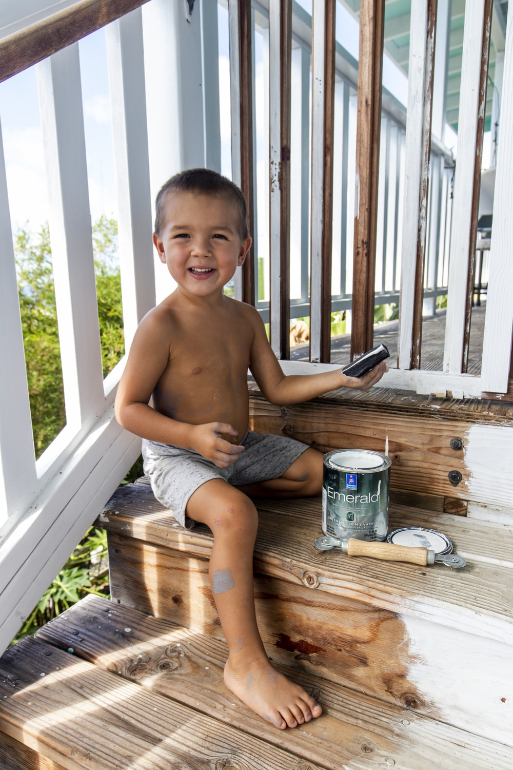 topless boy sitting on brown wooden bench