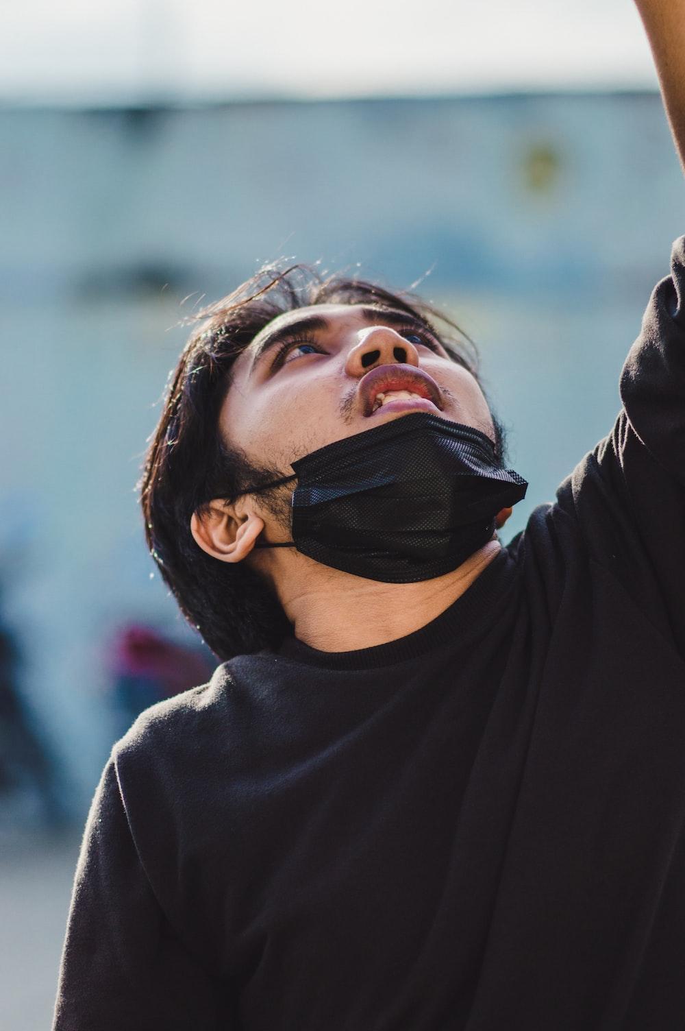 man in black turtleneck sweater wearing black mask