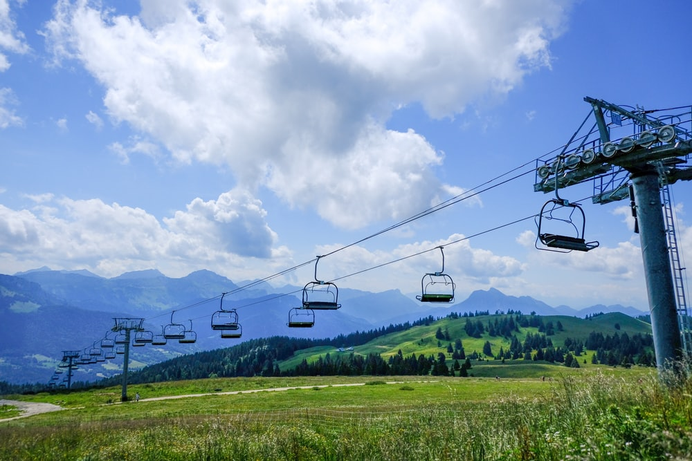 cable cars over green grass field during daytime