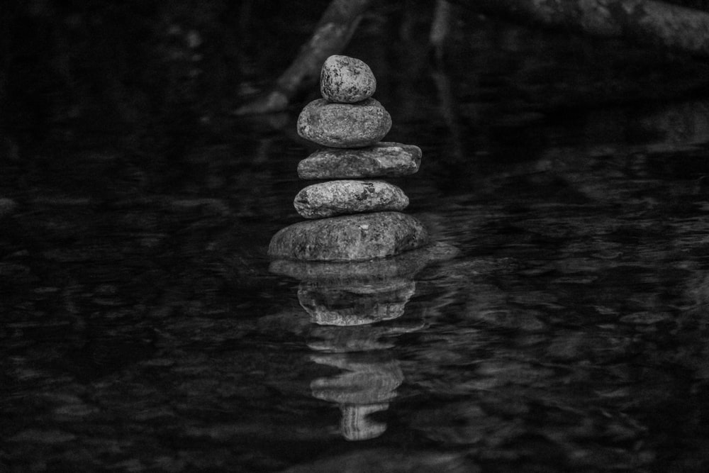 grayscale photo of stack of stones on water