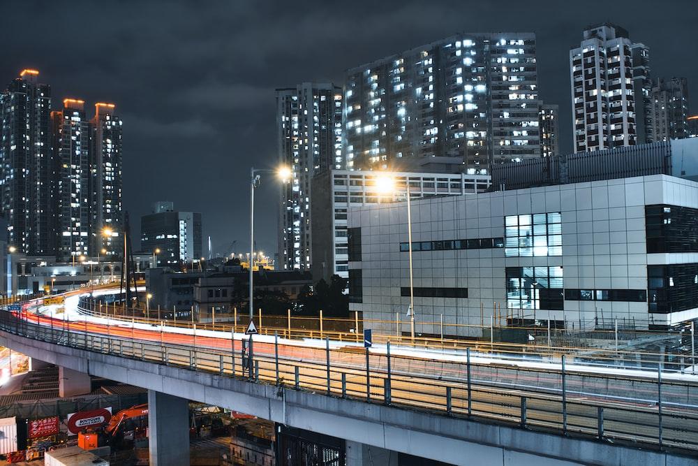 gray concrete bridge near city buildings during night time