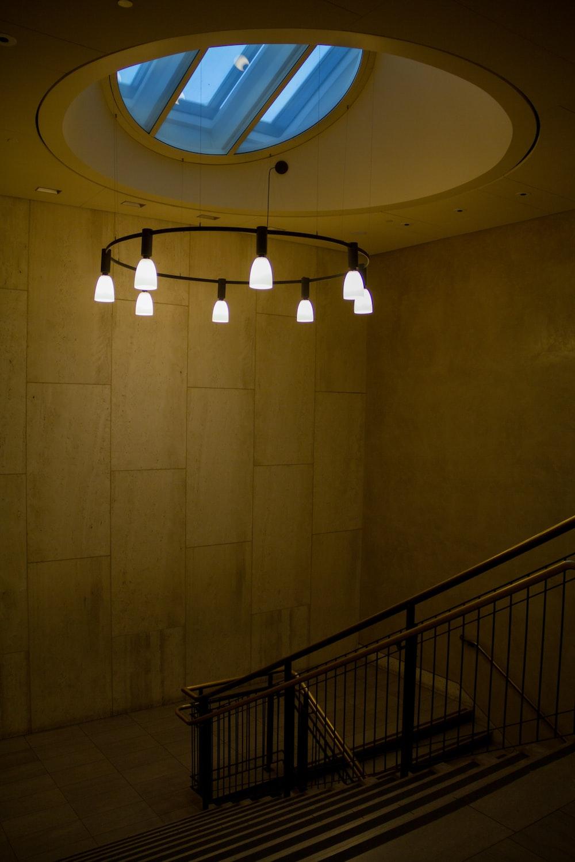 white ceiling light turned on near black metal railings