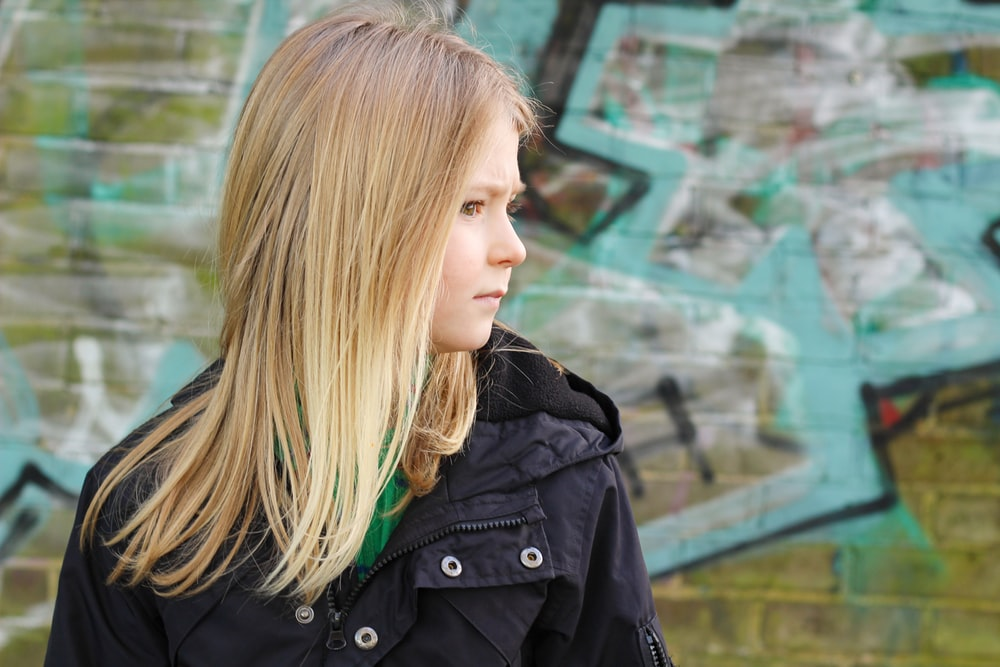 woman in black jacket standing near green wall