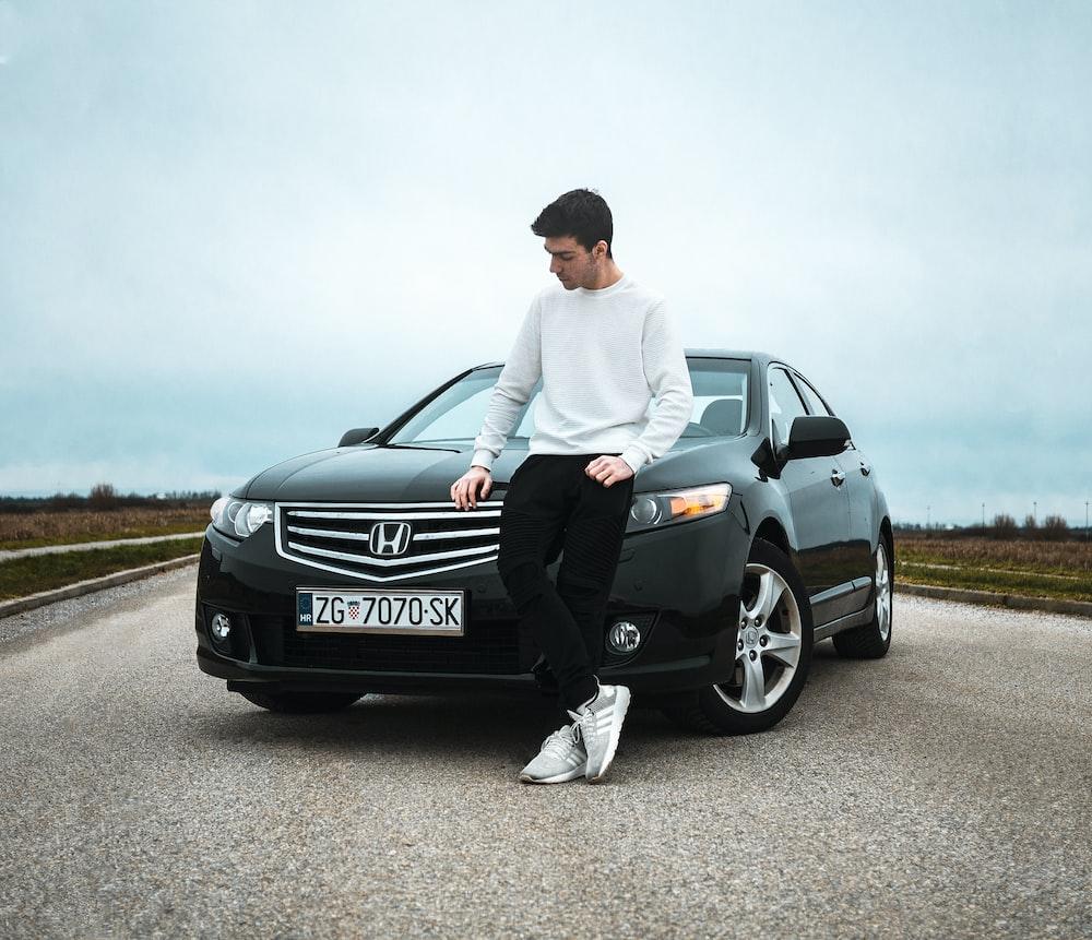 man in white dress shirt and black pants sitting on black mercedes benz car