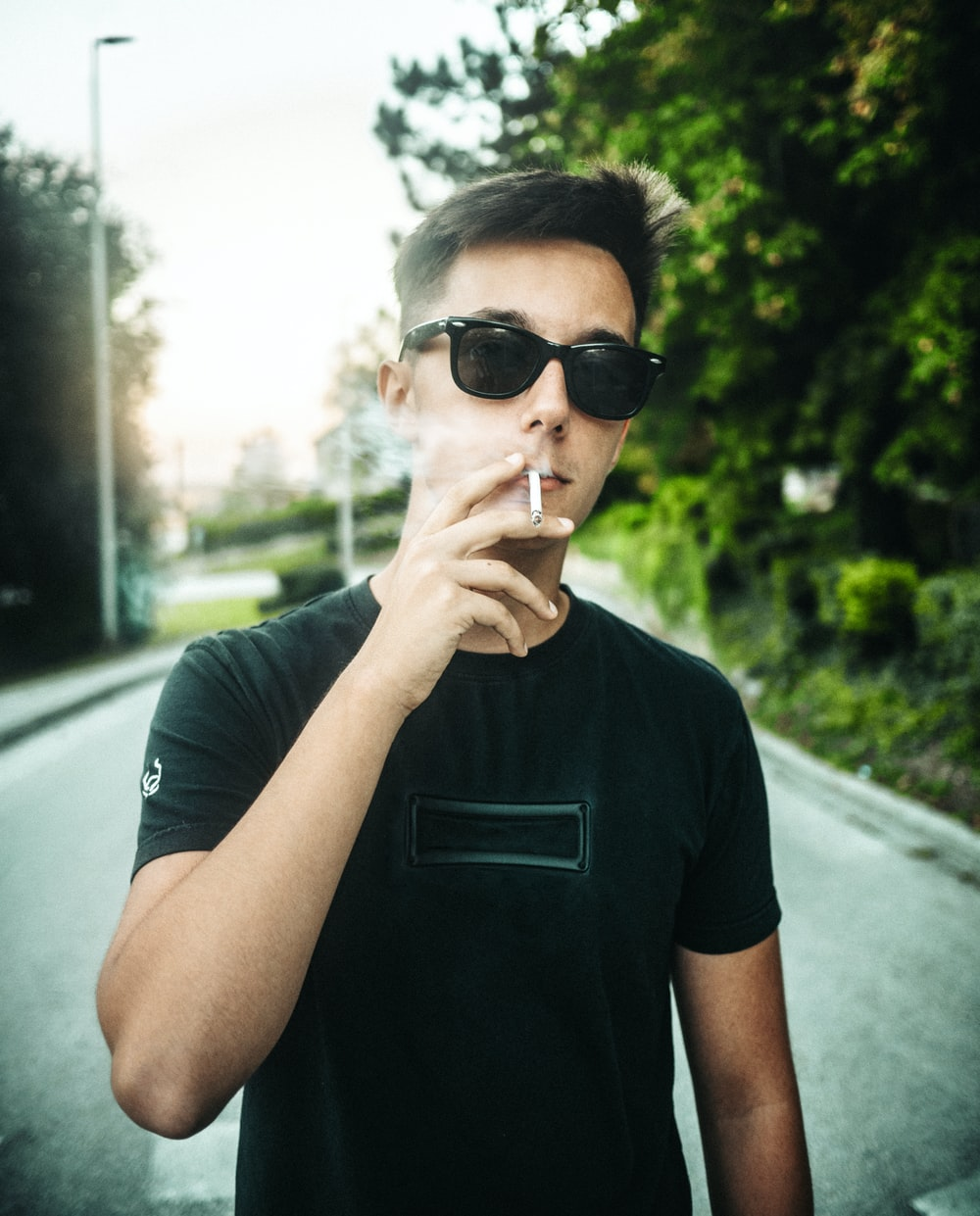 man in black crew neck t-shirt wearing black sunglasses
