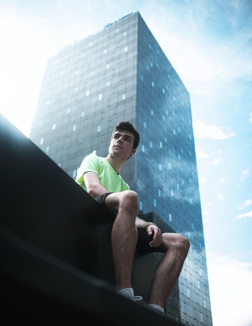 man in green t-shirt sitting on black concrete wall