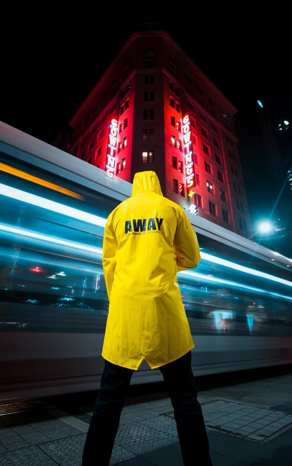 man in yellow hoodie standing on the street during night time