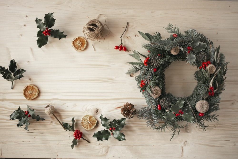 green and red wreath on white wooden wall