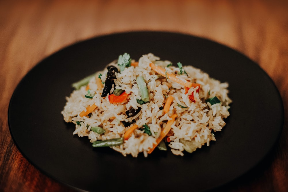 white rice with green leaf vegetable on black plate