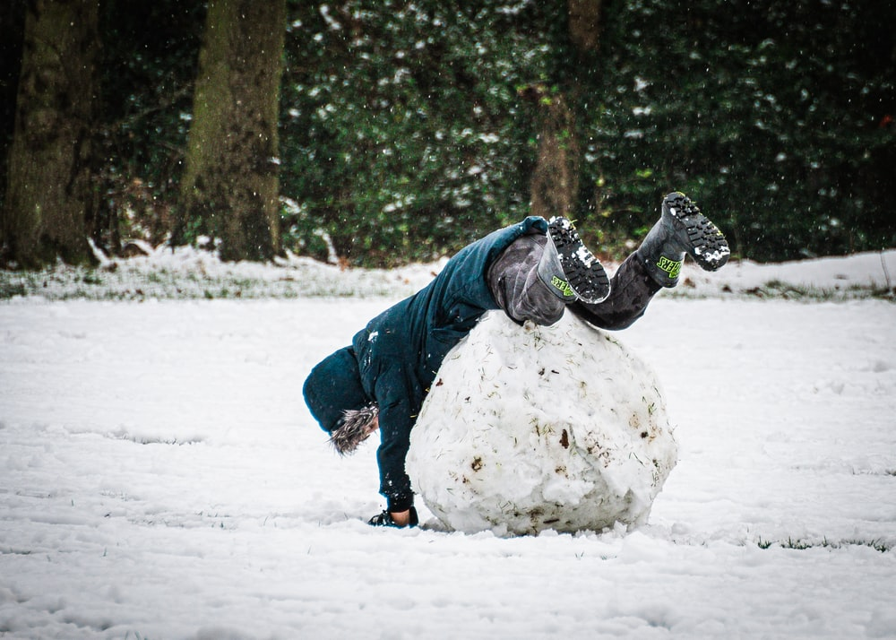 person in blue jacket and gray pants playing on snow covered ground during daytime