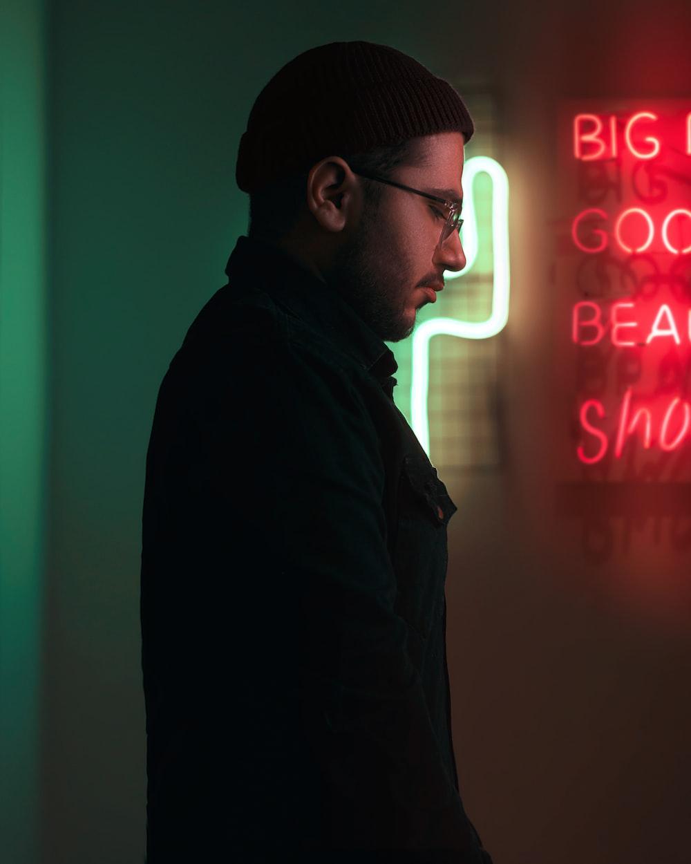 man in black jacket standing near neon sign