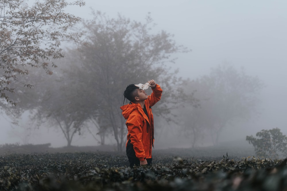 man in orange hoodie standing on black rock