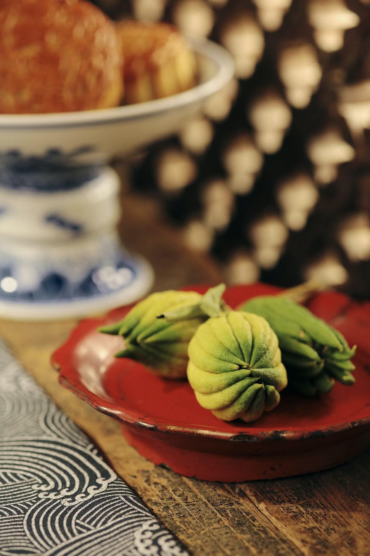 green leaves on red ceramic bowl