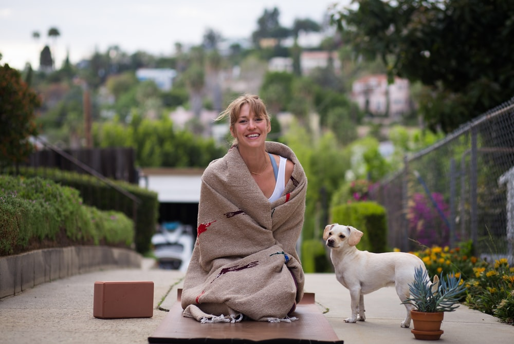 woman in brown robe sitting beside white short coated dog during daytime
