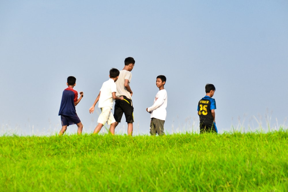 group of people standing on green grass field during daytime
