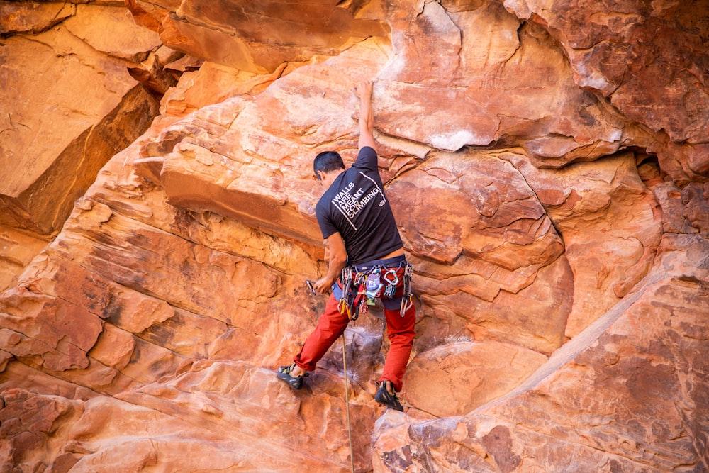 man in black t-shirt and orange shorts climbing brown rock formation during daytime