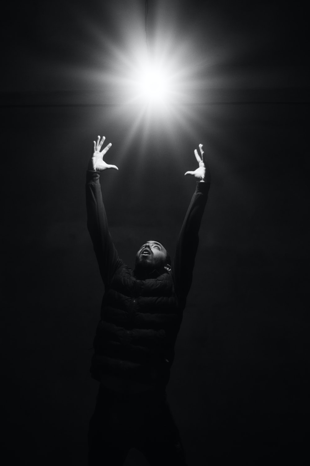 grayscale photo of man raising his hands