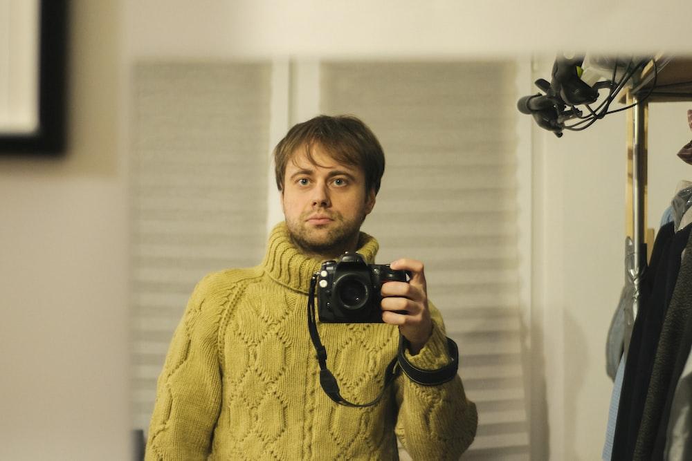 boy in yellow sweater holding black camera