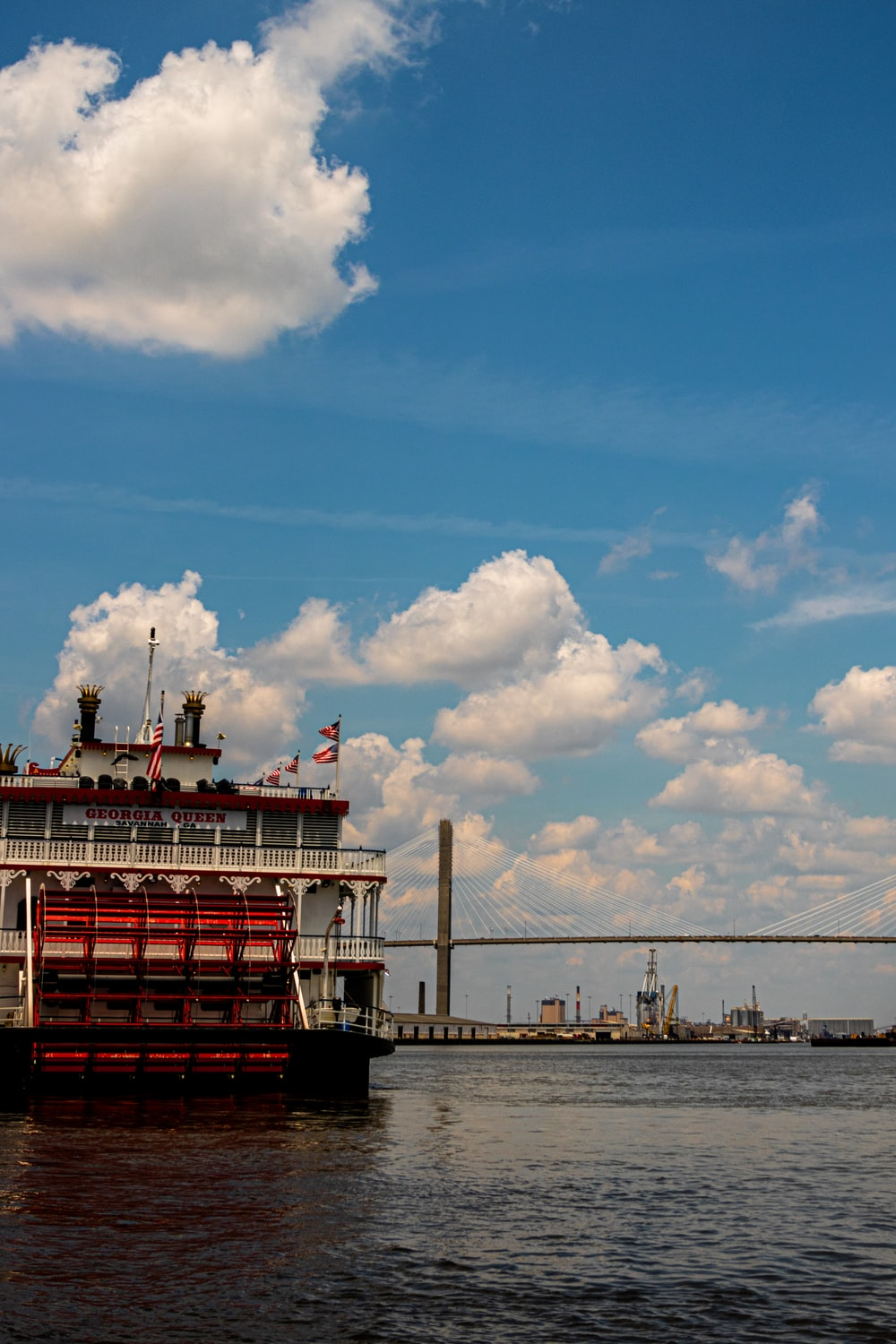 red and white ship on sea under blue sky and white clouds during daytime
