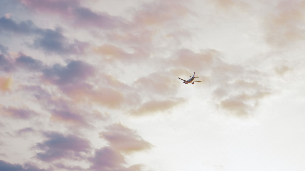 white airplane flying under cloudy sky during daytime