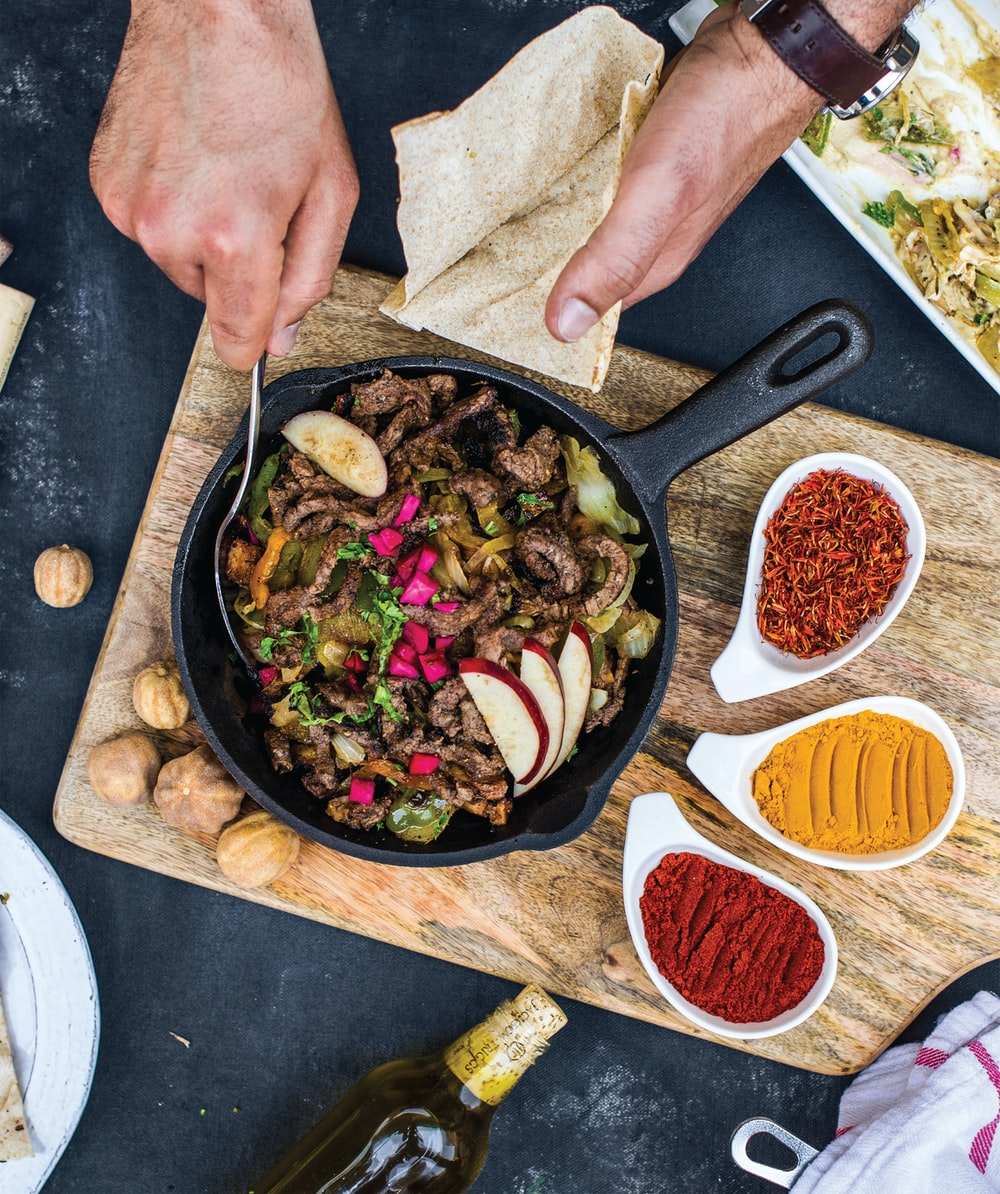person holding black frying pan with cooked food