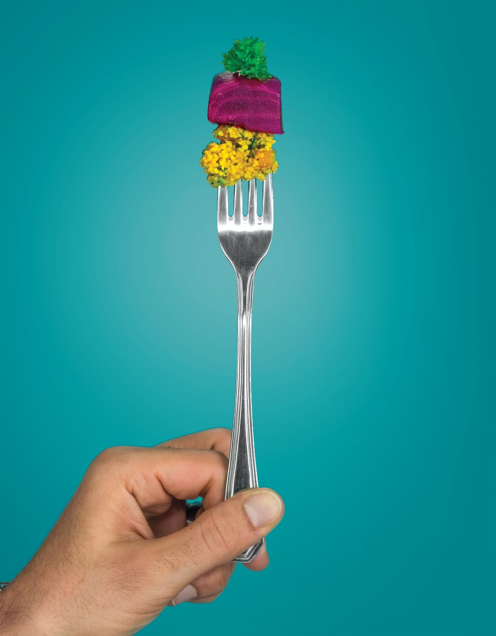 person holding stainless steel fork with purple and yellow ice cream