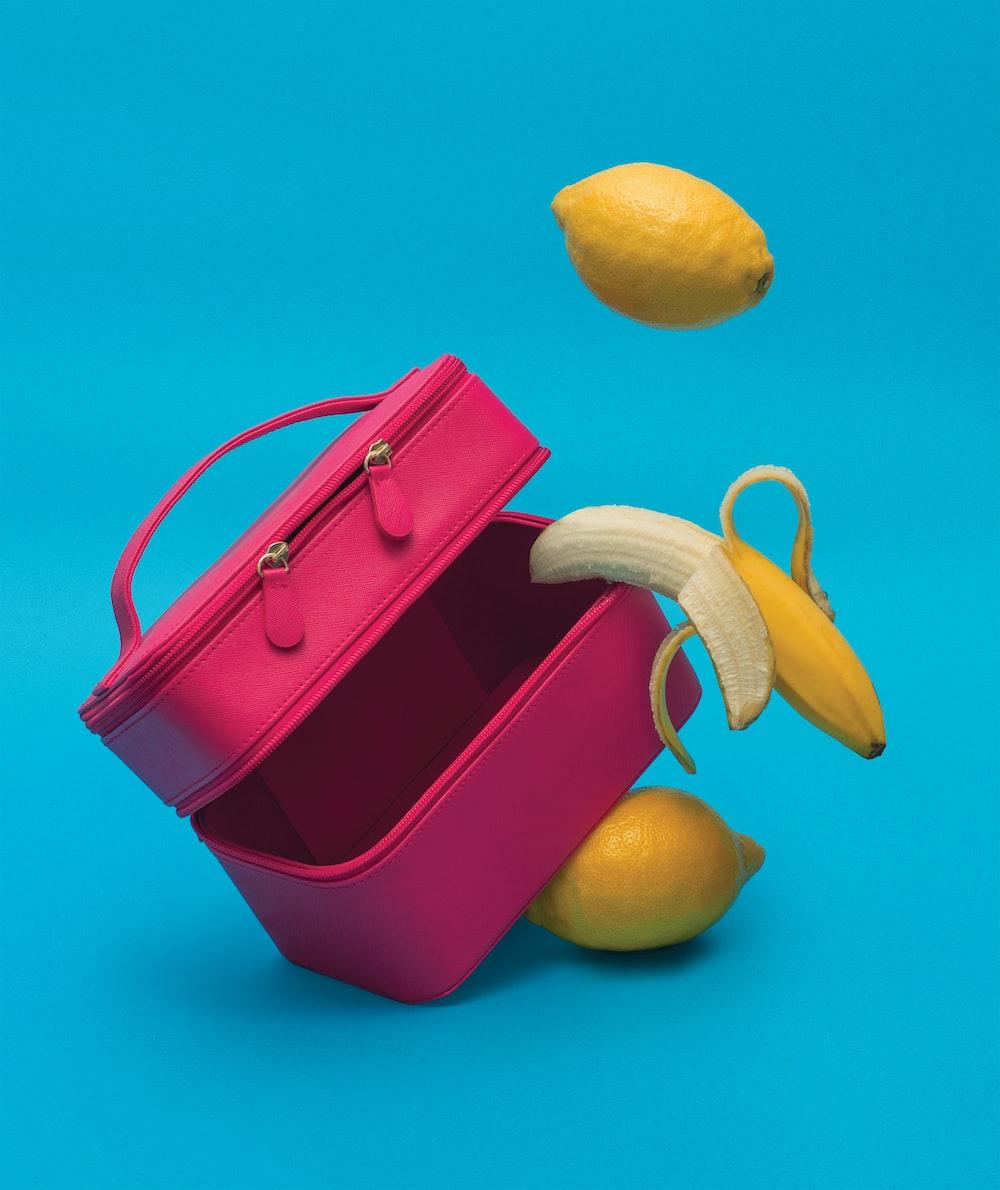 yellow lemon fruit on pink leather handbag