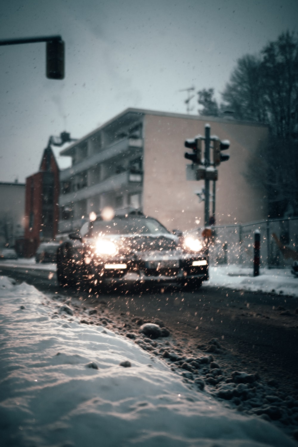black car on road covered with snow during daytime