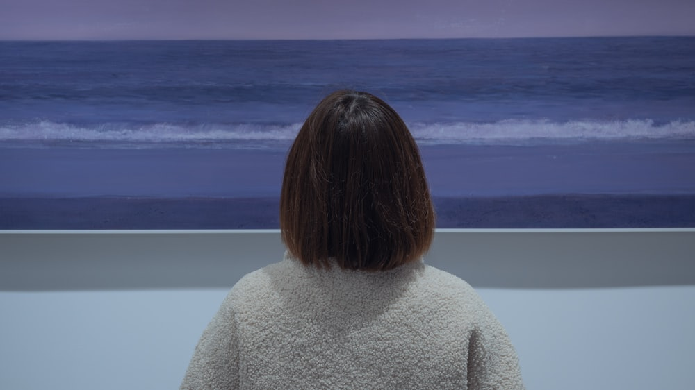 woman in gray sweater standing near body of water during daytime