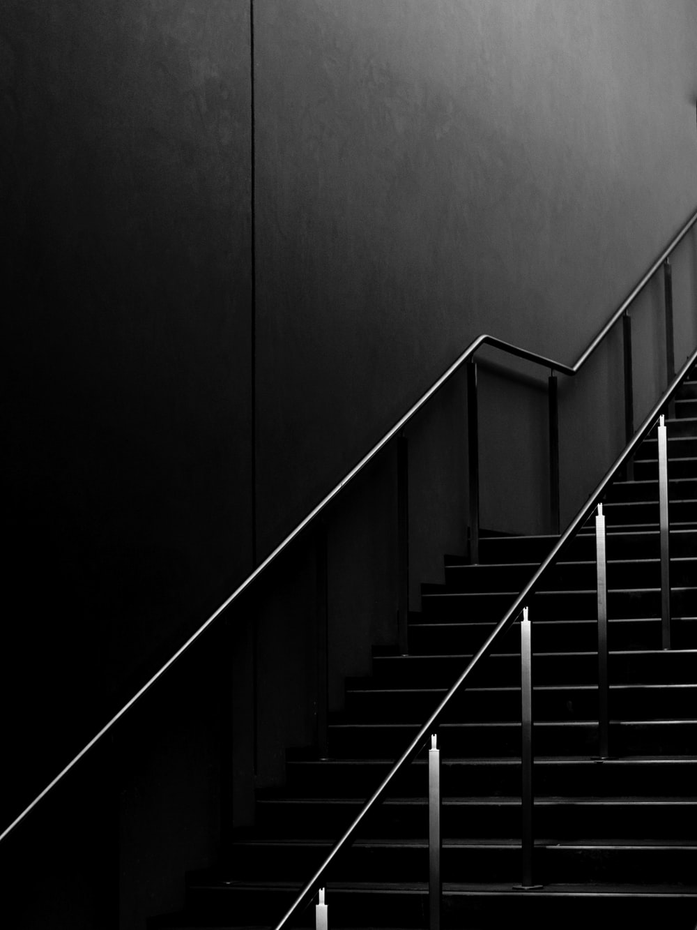 grayscale photo of staircase with railings