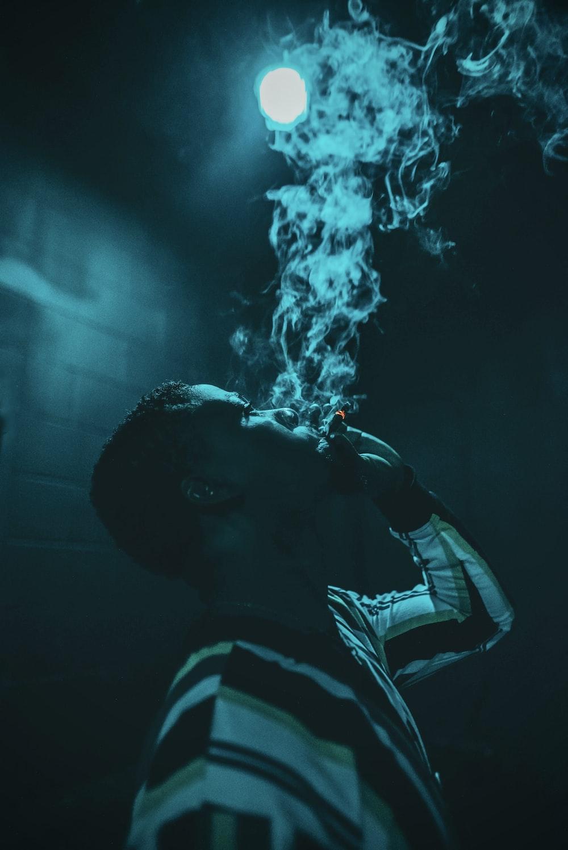 man in black and white striped shirt smoking